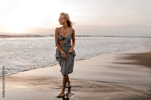Vászonkép Cool young blonde woman in stylish striped dress and pink sunglasses walk on beach, smiles and enjoys sunset