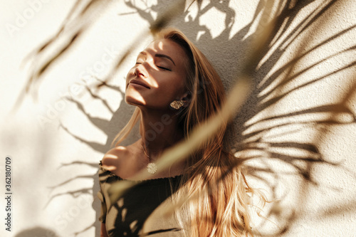 Cheerful young attractive woman in stylish dark-green top enjoys sunny weather, poses near white wall with palm leaf shadow and smiles. - fototapety na wymiar