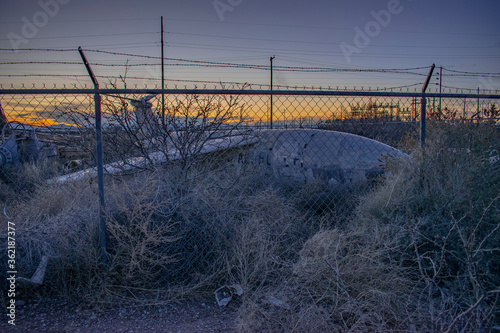 Photo Old military airfare aircraft in a junkyard during sunset in New Mexico