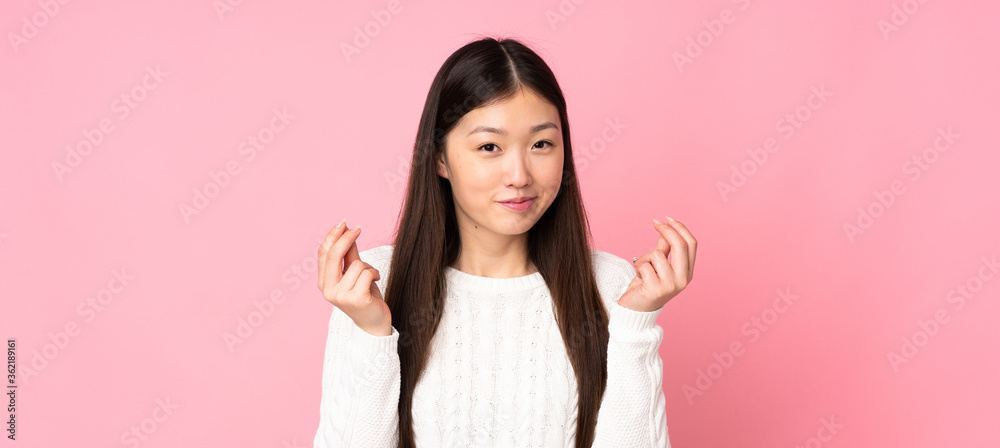 Fototapeta Young asian woman over isolated background making money gesture