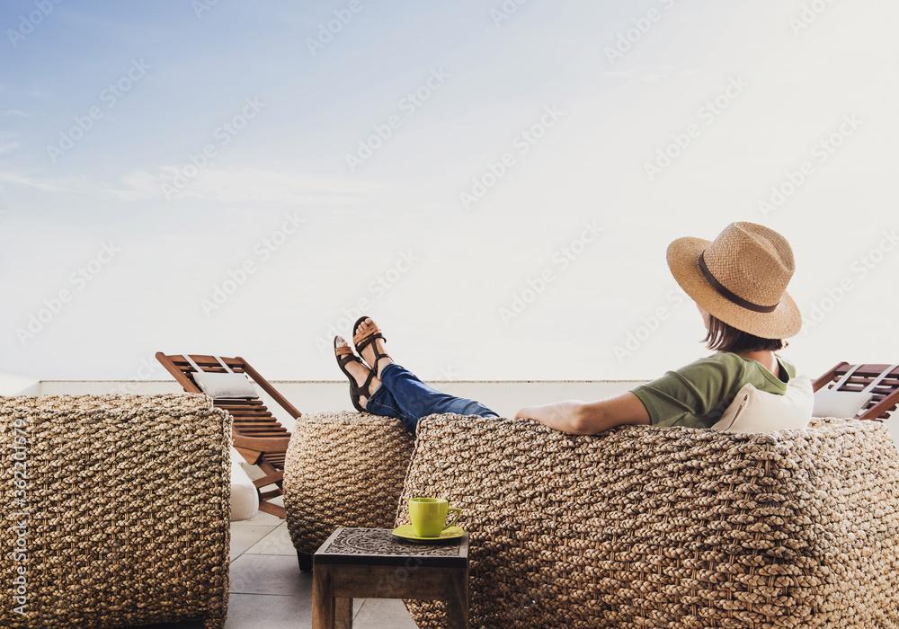 Fototapeta Young woman reslaxing on terrace at home. Beautiful girl enjoying life. Vacations, relaxation and summer fun concept - obraz na płótnie