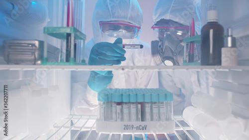 Cuadros en Lienzo Laboratory workers examining covid-19 blood sample from fridge
