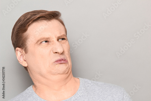 Portrait of funny man grimacing from disgust and squeamishness Fototapeta