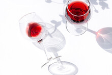 A Glass Of Red Wine Is Lying On The White Table With Leaves Shadows Modern Composition. Close Up