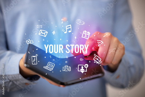 Fototapeta Businessman holding a foldable smartphone with YOUR STORY inscription, social media concept obraz