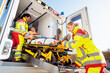 Leinwanddruck Bild - Paramedics putting injured man on stretcher in ambulance car
