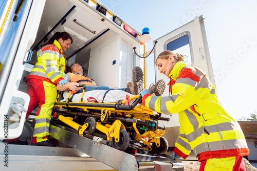 Paramedics putting injured man on stretcher in ambulance car