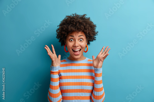 Obraz Portrait of delighted cheerful ethnic woman reacts on awesome gift, raises palms and stares with eyes full of happiness, cannot believe in her great success, dressed in casual wear, poses indoor - fototapety do salonu