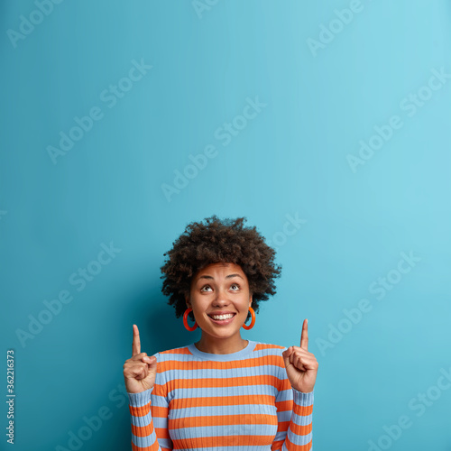 Cheerful African American woman looks up and points upwards with broad smile, recommends awesome product, suggests click banner, dressed casually, isolated on blue background shows advertisement promo