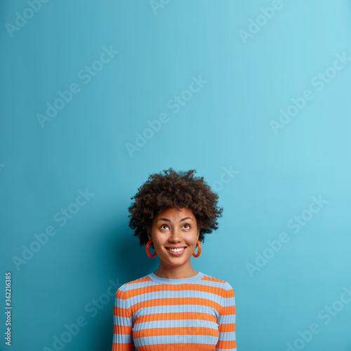 Vertical shot of good looking Afro American woman looks above with broad smile, notices nice offer or sale, feels happy dressed in casual striped jumper isolated on blue background. Copy space upwards Fotomurales