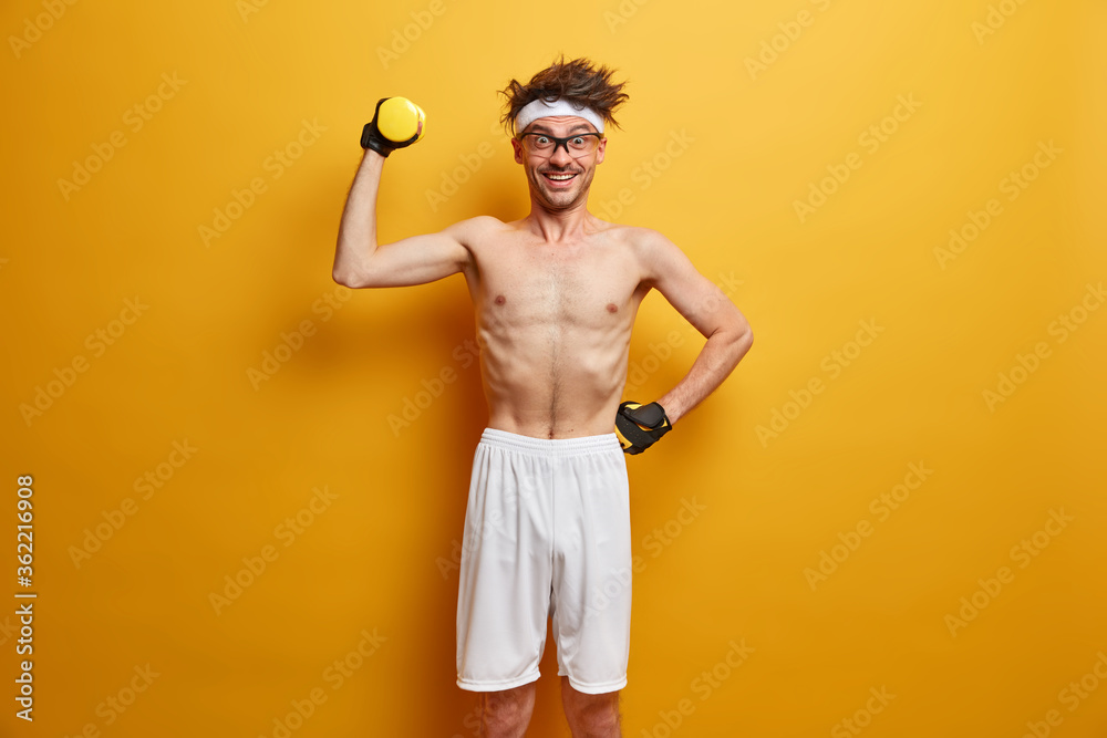 Fototapeta Sporty man makes easy exercise on biceps, raises hand with dumbbell, leads healthy lifestyle, being fitness instructor, smiles gladfully, motivates you to be strong, develops muscular strength