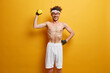 Sporty man makes easy exercise on biceps, raises hand with dumbbell, leads healthy lifestyle, being fitness instructor, smiles gladfully, motivates you to be strong, develops muscular strength
