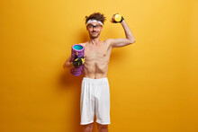 Nerd Man With Skinny Body Does Exercises With Dumbbell, Holds Foam Roller For Massage, Lifts Heavy Weight, Wears Spectacles And White Shorts, Visits Sports Center Regularly, Poses Against Yellow Wall