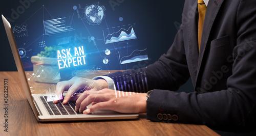 Fototapeta Businessman working on laptop with ASK AN EXPERT inscription, new business concept obraz
