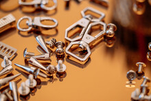 Silver Handbag Accessories, Rivets, Screws, Carabiners Placed On A Gold Reflective Plate