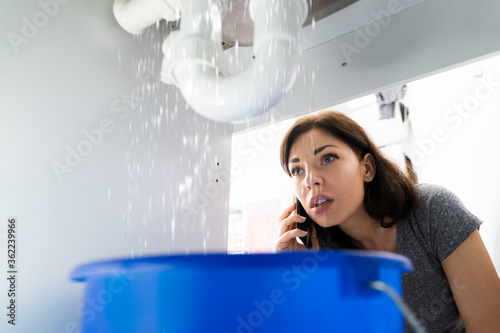 Women Doing Emergency Plumber Phone Call In Kitchen