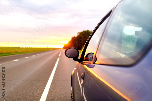 car trip concept. part of a moving car at sunset Wallpaper Mural