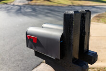 Closeup Back View Of Two Modern Black Mailboxes At Single Family Home In Residential Suburbs With Nobody And Street Road