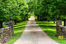 Gated Open Entrance With Road Driveway In Rural Countryside In Virginia Estate With Stone Fence And Gravel Dirt Path Street With Green Lush Trees In Summer