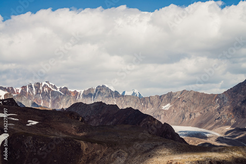 Obraz na plátně Atmospheric mountain landscape with rocky ridge with snow and glacier tongue in sunlight