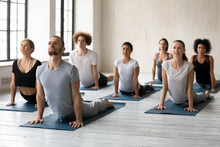 Male Trainer Doing Bhujangasana Cobra Pose With Motivated Sporty Young Multiethnic People In Activewear At Yoga Studio Interior, Stretching Back Muscles On Mats, Working Out Together Indoors.