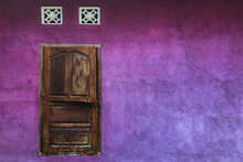 Bright Purple Shabby Wall With Closed Wooden Shutters Window. Colorful Architecture, Old And Vintage Style. Empty Place For Text.