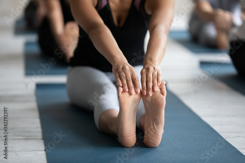 Close up front view young barefoot biracial woman sitting on yoga mat, touching feet with hands, practicing seated forward bend exercise position at group pilates fitness class in sports club gym. - 362292397