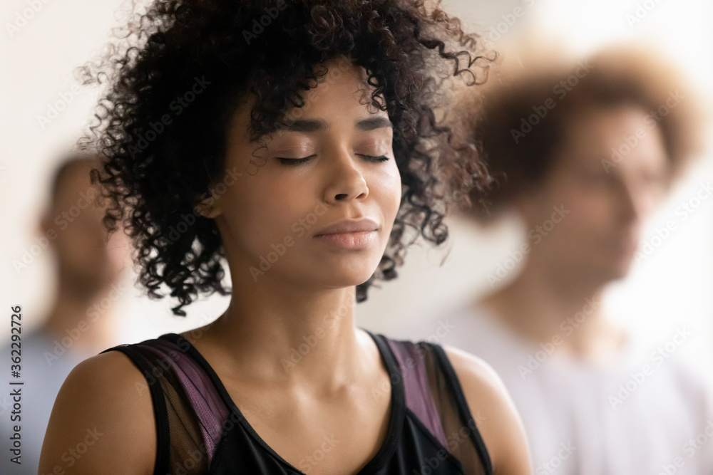Fototapeta Head shot close up young peaceful attractive curly hair african american woman breathing fresh air, enjoying deep meditation with closed eyes, relaxing after yoga class workout in sport club.