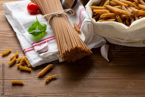 Fotografering Whole grain uncooked pasta spaghetti and penne in cotton bag on wooden table