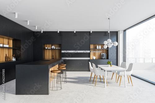 Fotografia Black kitchen with bar, table and balcony
