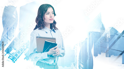 Serious young woman with notebook in city - 362301531