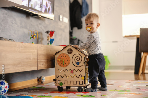 Adorable toddler playing interactive games for good development at home.