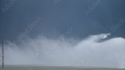 Fototapeta Massive waves crash over harbour wall onto lighthouse during huge storm on English coastline in Newhaven, amazing images showing power of the ocean obraz
