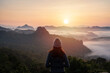 Leinwanddruck Bild - Young woman traveler looking at sea of mist and sunset over the mountain
