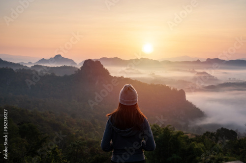 Young woman traveler looking at sea of mist and sunset over the mountain - 362316127