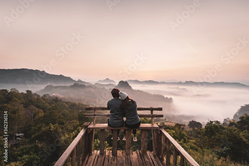 Fototapeta Young couple traveler looking at sea of mist and sunset over the mountain at Mae Hong Son, Thailand obraz