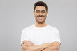 Young handsome man wearing white t-shirt, round glasses and wireless earphones, standing with crossed arms, smiling confidently, isolated on gray background