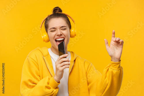 Fotografía Young girl in yellow hoodie and wireless headphones, singing with closed eyes, h