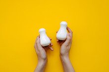 Human Hands Holding Minimalist White Salt And Pepper Shakers On Clean Yellow Background.