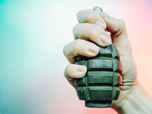 A Closeup Photo Of A Hand Squeezes A Green Military Grenade On A Multicolor Background.