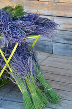 Lavender Decoration, Bunch Of Purple Flowers With Stalks On A Yellow Table, Blurred Wooden Background