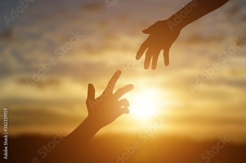Obraz na plátně Silhouette of giving a helping hand, hope and support each other over sunset background