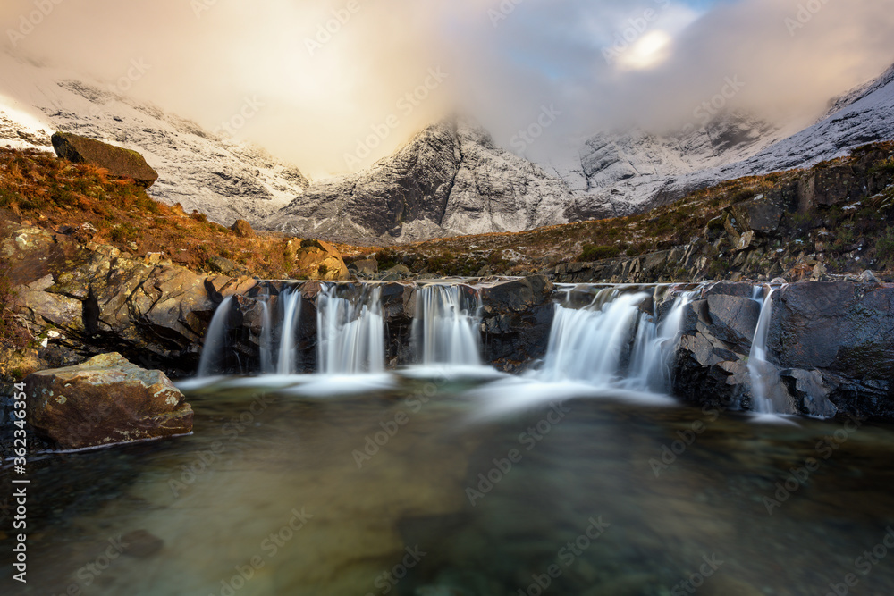 Fototapeta Stunning cascade waterfall at the Fairy Pools on the Isle of Skye in the Scottish Highlands. Taken in the evening golden hour, beautiful light from the sun can be seen in the Winter landscape.