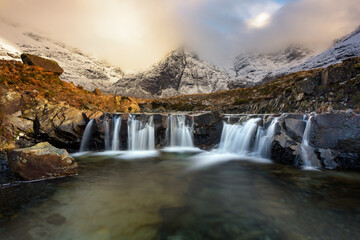 Stunning cascade waterfall at the Fairy Pools on the Isle of Skye in the Scottish Highlands. Taken in the evening golden hour, beautiful light from the sun can be seen in the Winter landscape.