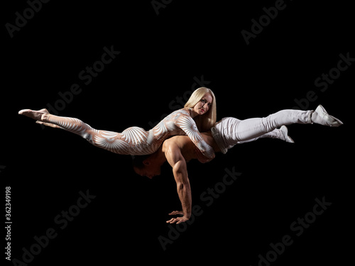 Fototapeta Couple acrobats perform a trick handstand, body balance, isolated on a black background. A girl in a white suit, a guy with a naked muscular torso and white pants. obraz