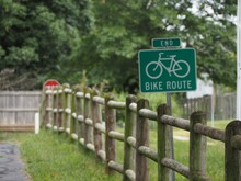 Green Bike Route Sign Near The Wooden Fence