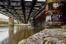 Underneath Old Iron Railway Bridge Over River Eden Carlisle Cumbria With Graffiti On Stone Pillars