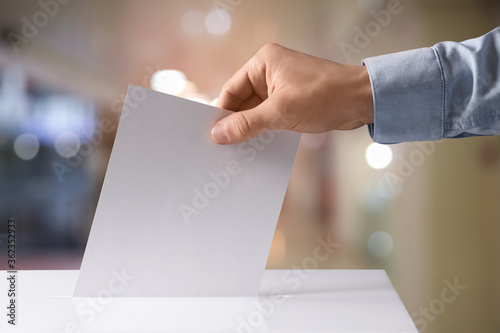 Valokuva Man putting his vote into ballot box indoors, closeup