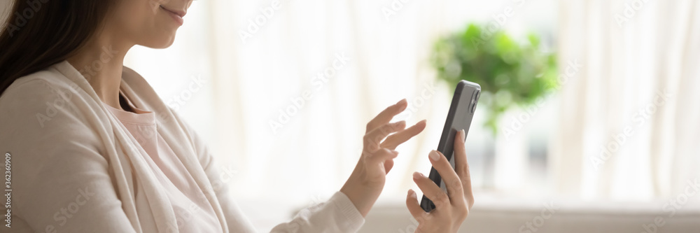Fototapeta Satisfied young woman holding smartphone, browsing mobile device app close up cropped wide image, beautiful girl using phone, writing message in social network, shopping online, playing game