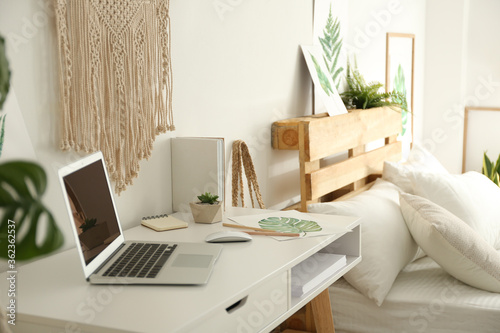Fototapeta Stylish room interior with workplace and bed obraz